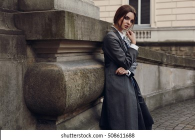 Fashionable Woman In High Fashion Clothes Standing In Street. Beautiful Sexy Girl In Womanly Stylish Clothing Posing Outdoors. Portrait Of Female Model In Elegant Overcoat, Shirt, Skirt, Tie In Autumn