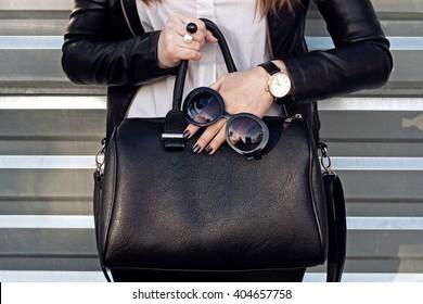 Fashionable woman hold big black handbag , accessories, sunglasses, watch. Street style city wall background