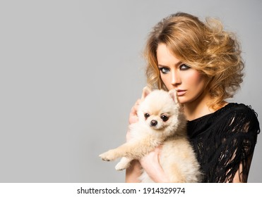 Fashionable woman with little dog. Dogs love. Beautiful young woman holding puppy on hands. National pet's day. Love animals