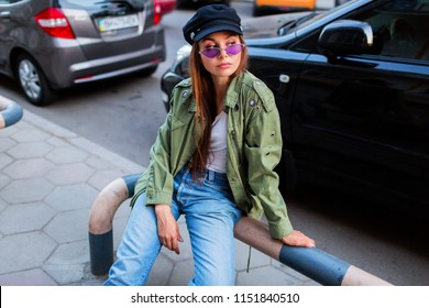 Fashionable woman with long brunet hairs posing outdoors in big  city near road . Wearing stylish green jacket , black cap and purple sunglasses.