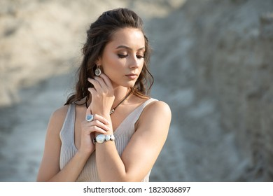 Fashionable woman with long hair wears trendy hoop earrings, silver necklace posing on the beach at sunset