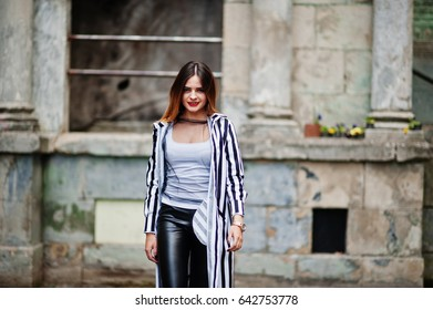 Fashionable woman look with black and white striped suit jacket, leather pants,  posing at old street. Concept of fashion girl.