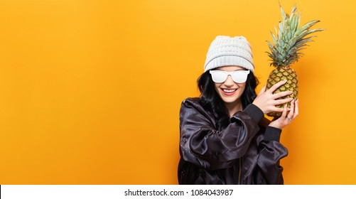Fashionable woman with pineapple on a solid background