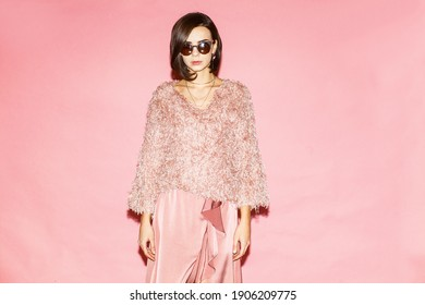 fashionable woman in pink clothing on pink background