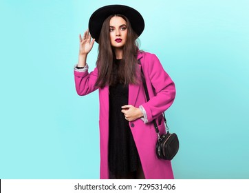 Fashionable woman in pink coat and black hat  on turquoise background, cold season. Autumn or winter look. Space for text. Studio shot.