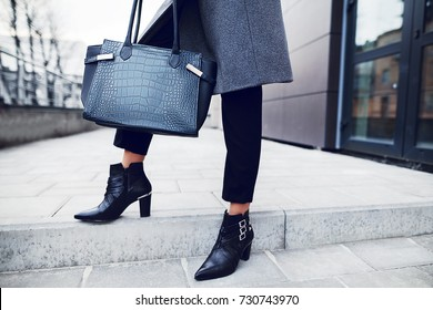 Fashionable woman posing in street, holding big dark blue textured bag, wearing stylish pointed toe ankle boots, elegant clothes. Female fashion concept. Copy, empty space for text.
