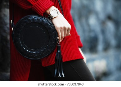 Fashionable woman posing in street, near wall, holding black round bag, wearing wrist watch, stylish red oversize sweater. Female fashion concept. Copy, empty space for text.