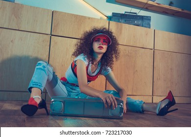 fashionable woman in red cap and high heels sitting near boombox on floor
