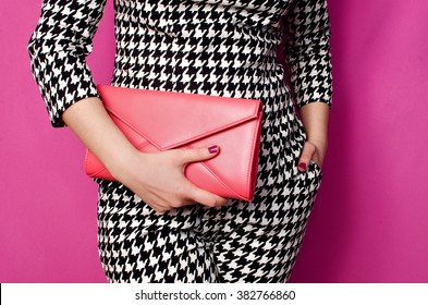 Fashionable woman with a red handbag in her hands and black white evening costume