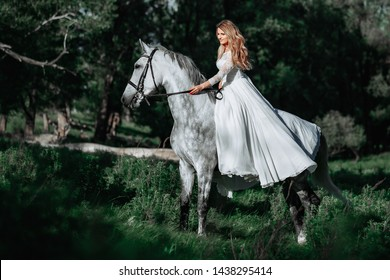 Fashionable woman riding a horse in sunny day. Long curly hair. Fashion colors.