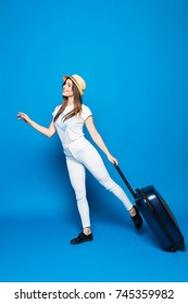 Fashionable woman running with suitcase on blue background