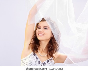 A fashionable woman standing with white material