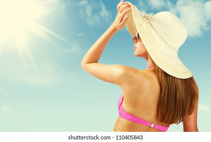 Fashionable woman with straw hat protects from sun