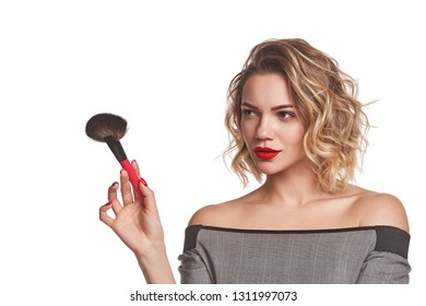 Fashionable woman stylist standing holding a makeup brush looking away at blank copy space, over white background