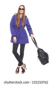 fashionable woman in sunglasses with handbag posing