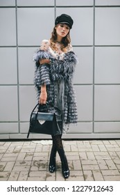 fashionable woman walking in city in warm fur coat, winter season, cold weather, wearing black cap, holding leather bag, street fashion trend