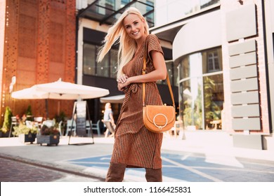 Fashionable woman walking in the street, wearing sunglasses, nice dress, high heels boots, handbag. Fashion urban autumn photo.