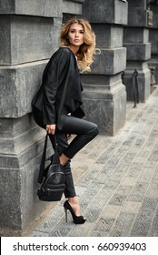 Fashionable woman wearing black leather clothes on a city street.