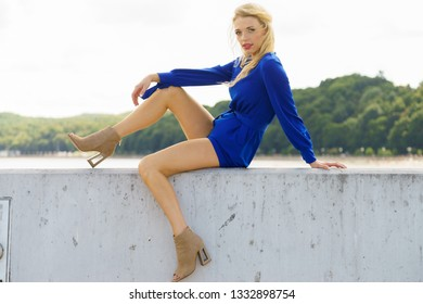 Fashionable woman wearing blue jumpsuit shorts perfect for summer. Fashion model outdoor photo shoot. Female relaxing in marina sitting