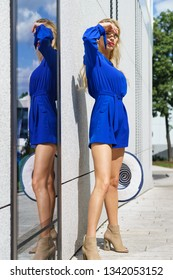 Fashionable woman wearing blue jumpsuit shorts perfect for summer holding elegant stylish sun hat. Fashion model outdoor photo shoot