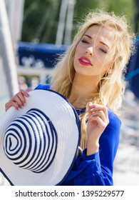 Fashionable woman wearing blue jumpsuit shorts perfect for summer holding elegant stylish sun hat. Fashion model outdoor photo shoot in marine
