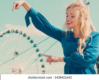 Fashionable woman wearing blue jumpsuit shorts perfect for summer. Fashion model outdoor photo shoot posing against ferris wheel