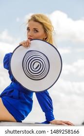 Fashionable woman wearing blue jumpsuit shorts perfect for summer holding elegant stylish sun hat.