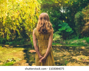 A fashionable woman wearing a dress is standing by a pond in a garden