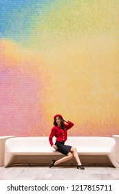 Fashionable woman wearing red in front of colorful wall