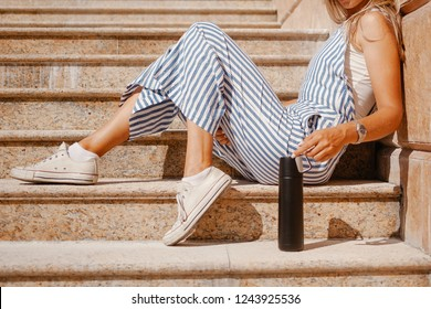 Fashionable woman wearing striped overalls holds a black tumbler bottle