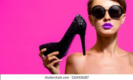 Fashionable woman wearing sunglasses holding high heels