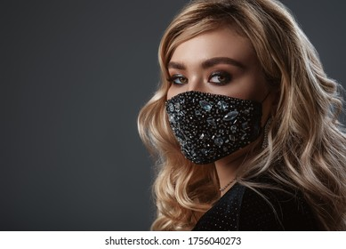 Fashionable woman wearing trendy  luxury face safety black mask with rhinestones. Stylish outfit during quarantine of coronavirus outbreak.  Close up portrait. Copy, empty space