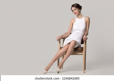 Fashionable woman in a white dress is sitting on a chair. Bright makeup