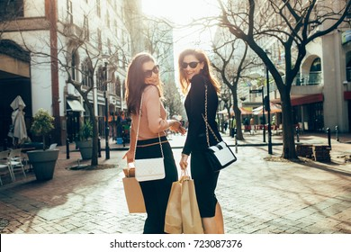 Fashionable women out on the street with shopping bags. Best friends shopping in the city. Two female standing outdoors carrying shopping bags looking over the shoulder and smiling.