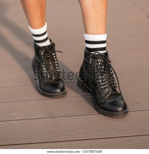 Fashionable women's black autumn-spring leather boots. New collection of stylish women's shoes. Casual design. Close-up of female legs.