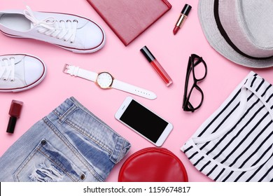 Fashionable women's clothes with smartphone and accessories on pink background