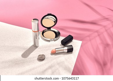 Fashionable Women's Cosmetics and Accessories. Flat Lay. Pink and white background. Shadow from a palm leaf