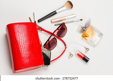 Fashionable women's handbag. Open red ladies handbag with scattered accessories.