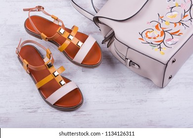 Fashionable women's sandals and backpack on white wooden background.