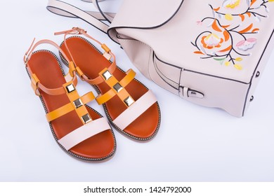 Fashionable women's sandals and backpack on white background.