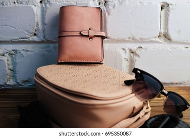 Fashionable women's wallet, leather bag and other accessories on a white brick wall background. Fashionable look.