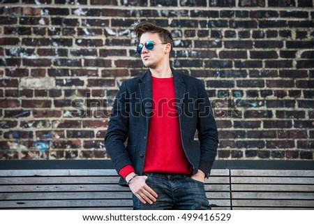 70192e8915 Fashionable young adult stylish man posing outdoors wearing red pulower,  jeans, cotton jacket and