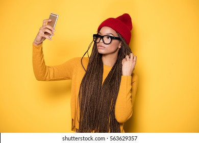 Fashionable young african american girl wearing red cap posing on yellow background, doing a selfie.