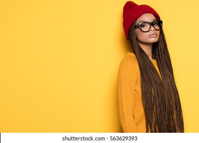 Fashionable young african american girl wearing red cap posing on yellow background.