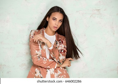 Fashionable young african american woman with glamour makeup and long hair posing in studio.