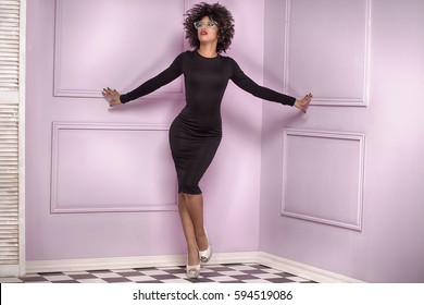 Fashionable young beautiful african american woman with afro hairstyle posing in elegant black dress. Pink room.