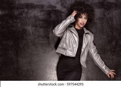 Fashionable young beautiful african american woman posing in silver jacket.