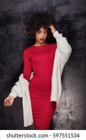 Fashionable young beautiful african american woman with afro hairstyle posing in elegant red dress.