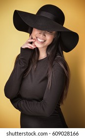 Fashionable young beautiful asian woman wearing black hat posing on yellow background.