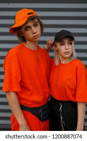 Fashionable young beautiful couple with caps in bright orange fashionable clothes near the metal gray wall. Fashion man and woman